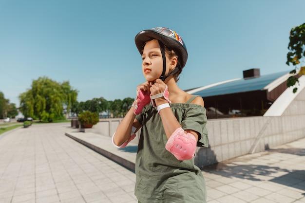 Teenager-mädchen in einem helm lernt, auf rollschuhen zu fahren, die eine balance halten oder inlineskaten und sich an einem sonnigen sommertag auf der straße der stadt drehen