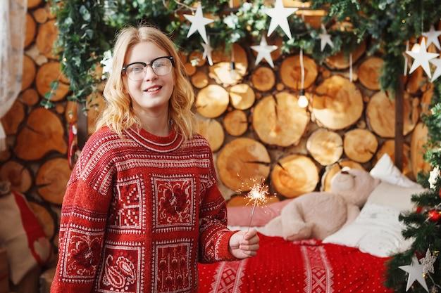 Teenager-mädchen in einem roten weihnachtspullover mit brennenden wunderkerzen in der hand in einem festlichen interieur.
