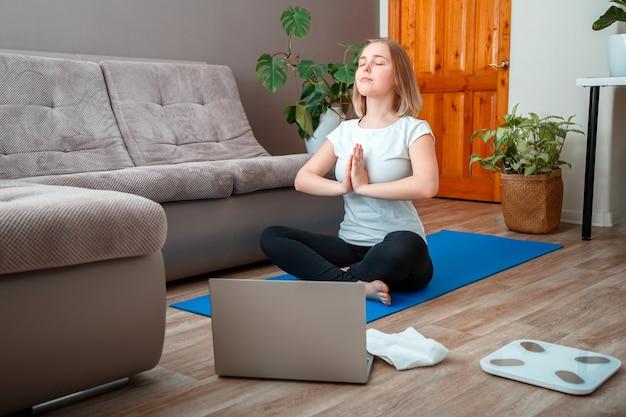 Teenager-mädchen in sportbekleidung machen remote-yoga-kurse im lotussitz während des aufenthalts zu hause. junge frau macht yoga-übungen im wohnzimmer in der nähe des sofas mit laptop. meditation reduziert stress wellness.