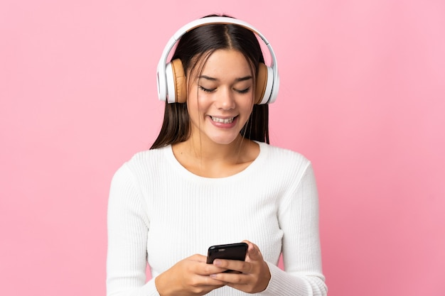 Teenager-mädchen isoliert auf blau hörende musik und auf handy schauend