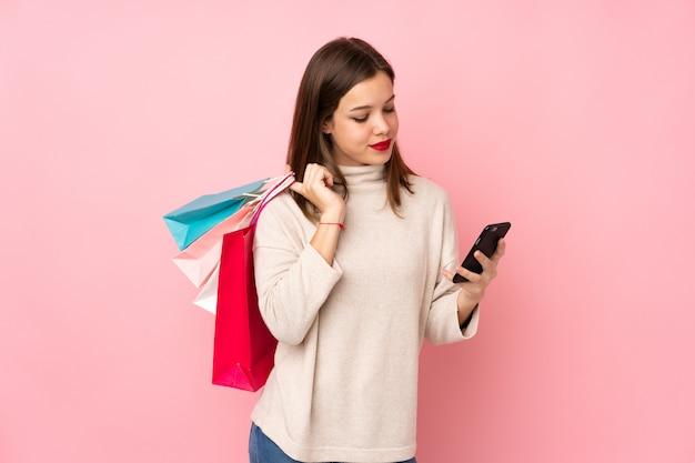 Teenager-mädchen isoliert auf rosa wand, die einkaufstaschen hält und eine nachricht mit ihrem handy an einen freund schreibt