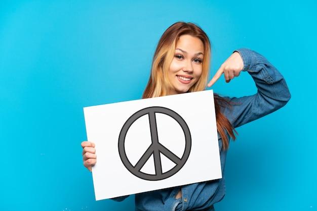 Teenager-mädchen isoliert ein plakat mit friedenssymbol halten und darauf zeigen