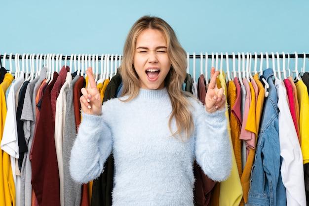 Teenager-mädchen kauft einige kleider an der blauen wand mit den fingern, die kreuzen