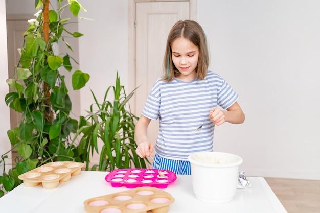 Teenager-mädchen legt den teig in silikonform für cupcakes zu hause