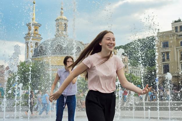 Teenager-mädchen, leute, die spaß im stadtbrunnen haben, planschen, nasse kleidung