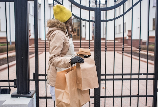 Teenager-mädchen liefert während der epidemischen coronovirus einige lebensmittel an eine ältere person.