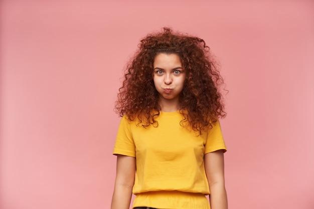 Teenager-mädchen, lustig aussehende frau mit gelockten ingwerhaaren, die gelbes t-shirt tragen