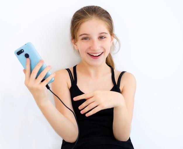 Teenager-mädchen mit blauem smartphone