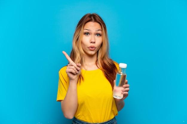 Teenager-mädchen mit einer flasche wasser über isoliertem blauem hintergrund, der beabsichtigt, die lösung zu realisieren, während ein finger anhebt