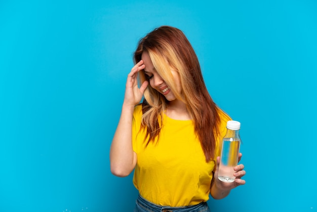 Teenager-mädchen mit einer flasche wasser über isoliertem blauem hintergrund lachen