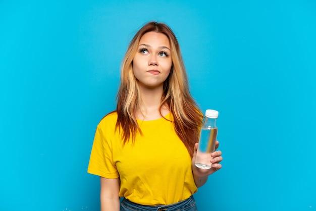 Teenager-mädchen mit einer flasche wasser über lokalisiertem blauem hintergrund und nach oben schauend
