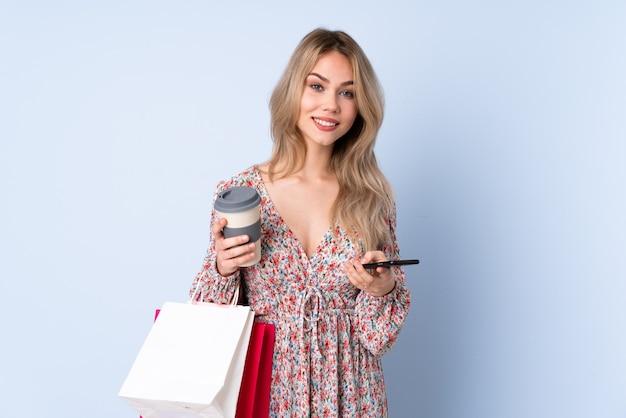 Teenager-mädchen mit einkaufstasche lokalisiert auf blauem haltekaffee zum mitnehmen und einem handy