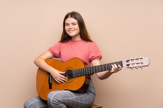 Teenager-mädchen mit gitarre viel lächelnd