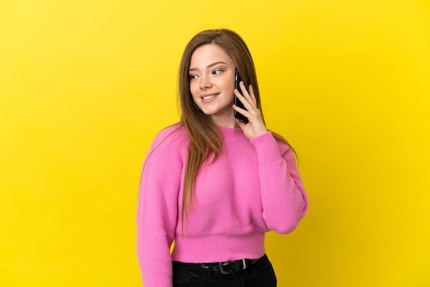Teenager-mädchen mit handy über isoliertem gelbem hintergrund, der zur seite schaut und lächelt