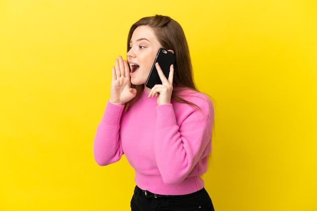 Teenager-mädchen mit handy über isoliertem gelbem hintergrund schreien mit weit geöffnetem mund zur seite
