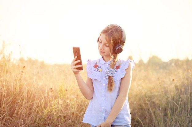 Teenager-mädchen mit kopfhörern, die smartphone in einer hand halten