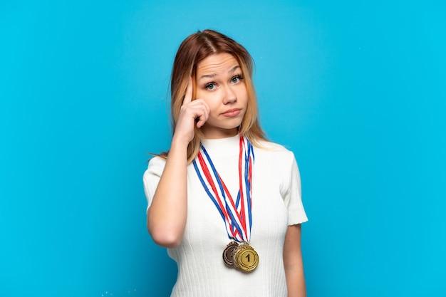 Teenager-mädchen mit medaillen über isoliertem hintergrund, der eine idee denkt