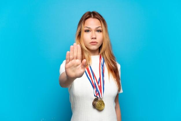 Teenager-mädchen mit medaillen über isoliertem hintergrund macht stopp-geste
