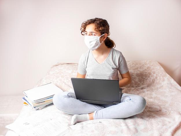 Teenager-mädchen mit medizinischer maske studiert online auf ihrem bett und schaut zum fenster