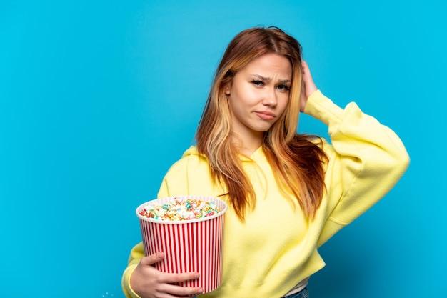 Teenager-mädchen mit popcorn isoliert mit zweifeln