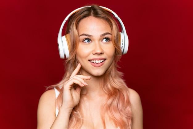 Teenager-mädchen mit rosa haaren, die musik über isoliertem rot hören