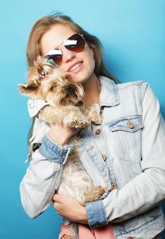 Teenager-mädchen mit yorkshire terrier über blauem hintergrund