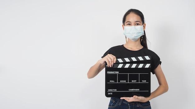 Teenager-mädchen oder asiatische junge frau tragen gesichtsmaske und handscharniere oder filmschiefer in der videoproduktion, film-, kinoindustrie auf weißem hintergrund.