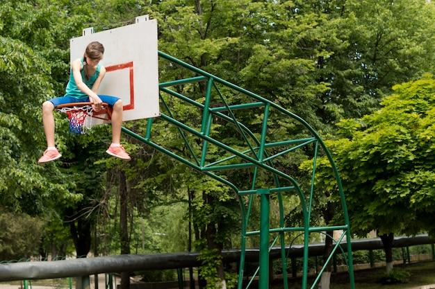 Teenager-mädchen repariert ein basketballnetz