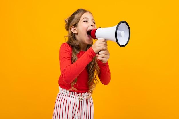 Teenager-mädchen schreien nachrichten in einem lautsprecher und steht seitlich auf gelb mit kopienraum