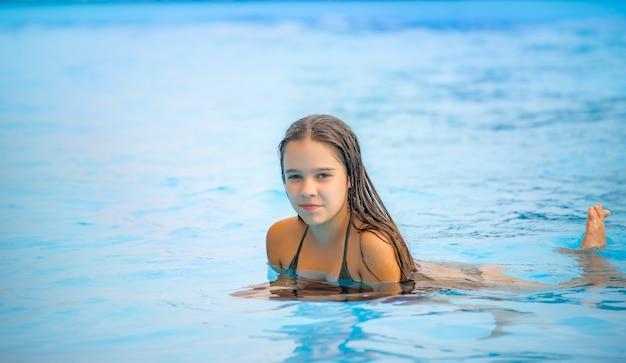 Teenager-mädchen schwimmt im klaren blauen wasser eines pools während eines urlaubs in einem warmen tropischen land an einem sonnigen warmen sommertag. reisekonzept. platz für werbung