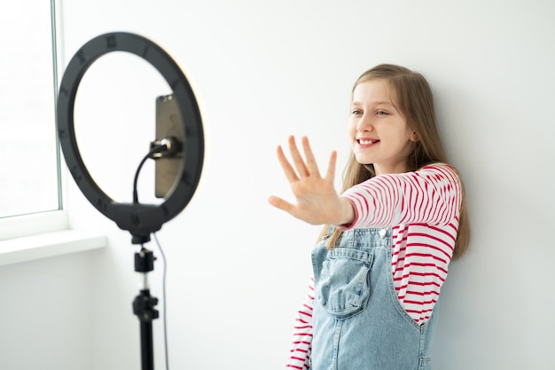 Teenager-mädchen-social-media-blogger, der video aufzeichnet, das smartphone auf stativ mit ringlicht betrachtet.