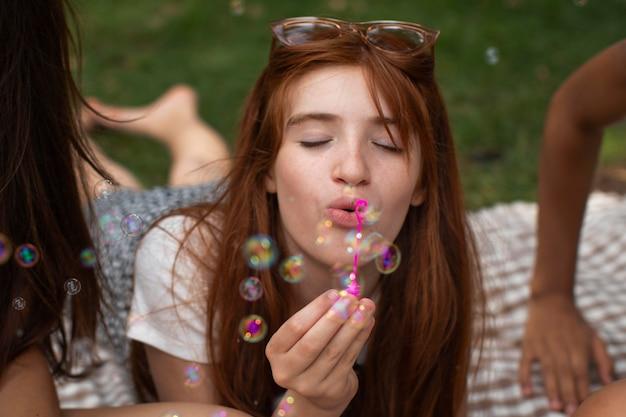 Teenager-mädchen spielt mit seifenblasen