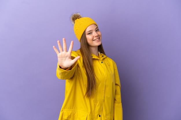 Teenager-mädchen trägt einen regendichten mantel über isoliertem lila hintergrund und zählt fünf mit den fingern