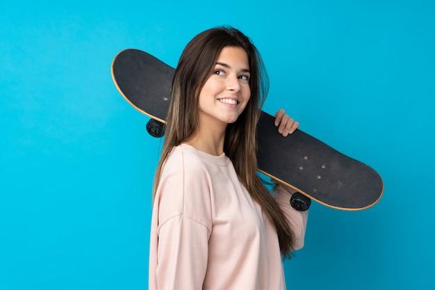 Teenager-mädchen über isolierte blaue wand mit einem skate mit glücklichem ausdruck