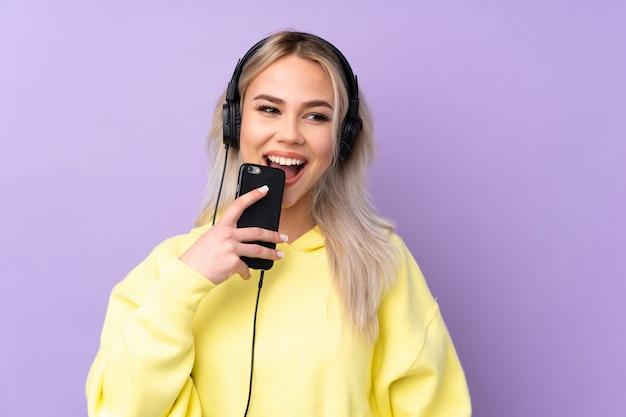 Teenager-mädchen über isolierte lila hörende musik mit einem handy und gesang