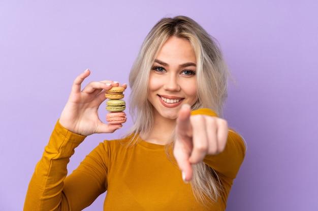 Teenager-mädchen über isolierte lila wand, die bunte französische macarons hält und finger auf sie zeigt