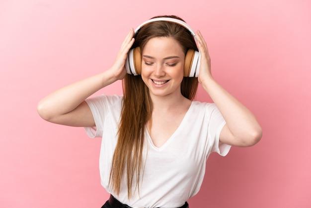 Teenager-mädchen über isolierte rosa hintergrund musik hören