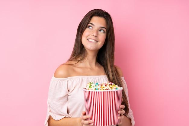 Teenager-mädchen über isolierte rosa wand, die einen großen eimer popcorn hält