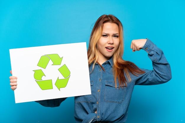 Teenager-mädchen über isoliertem blauem hintergrund, das ein plakat mit recycling-symbol hält und starke geste macht