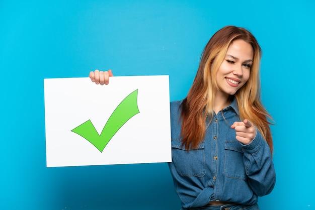 Teenager-mädchen über isoliertem blauem hintergrund, der ein plakat mit dem grünen häkchensymbol des textes hält und nach vorne zeigt