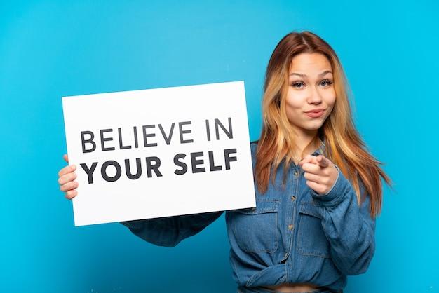 Teenager-mädchen über isoliertem blauem hintergrund, der ein plakat mit dem text believe in your self hält und auf die vorderseite zeigt