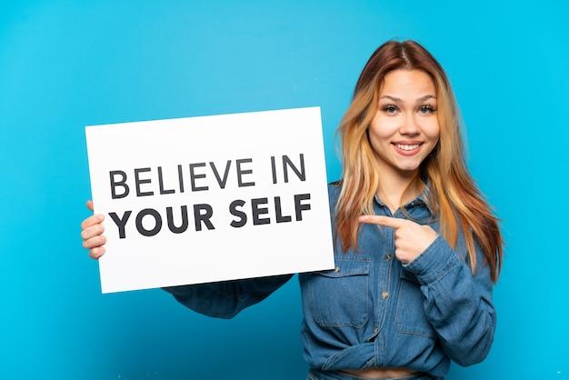 Teenager-mädchen über isoliertem blauem hintergrund, der ein plakat mit dem text believe in your self hält und darauf zeigt