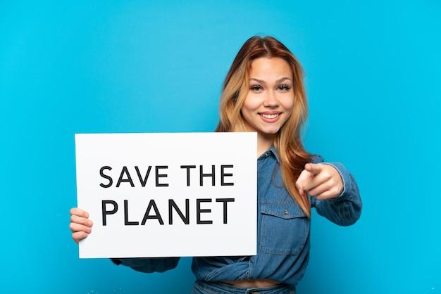 Teenager-mädchen über isoliertem blauem hintergrund, der ein plakat mit dem text save the planet hält und nach vorne zeigt