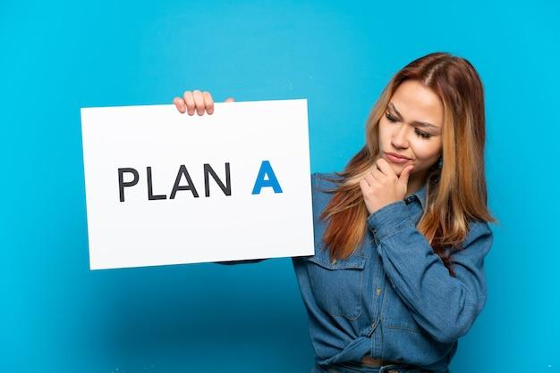 Teenager-mädchen über isoliertem blauem hintergrund, der ein plakat mit der nachricht plan a hält und denkt