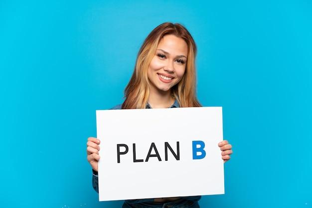 Teenager-mädchen über isoliertem blauem hintergrund, der ein plakat mit der nachricht plan b mit glücklichem ausdruck hält