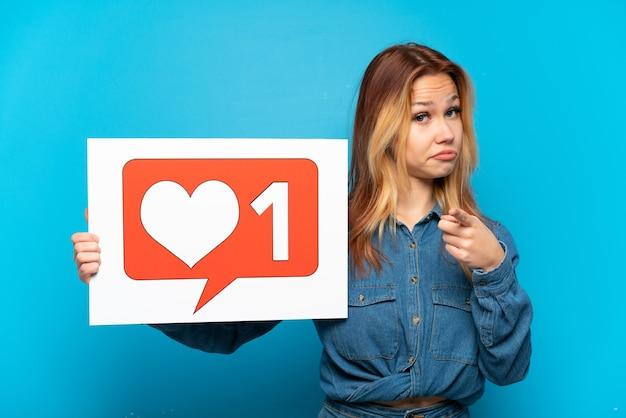Teenager-mädchen über isoliertem blauem hintergrund, der ein plakat mit like-symbol hält und nach vorne zeigt