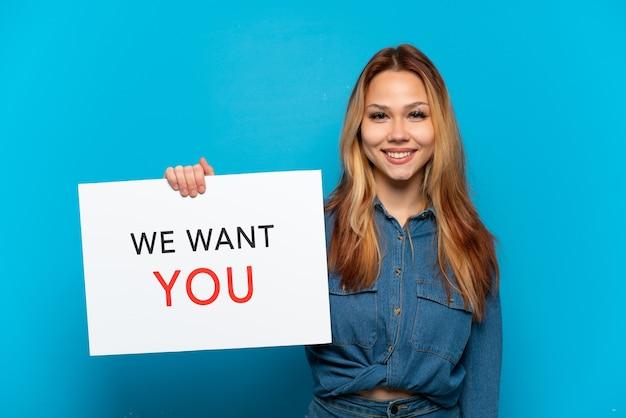 Teenager-mädchen über isoliertem blauem hintergrund, der we want you board mit glücklichem ausdruck hält