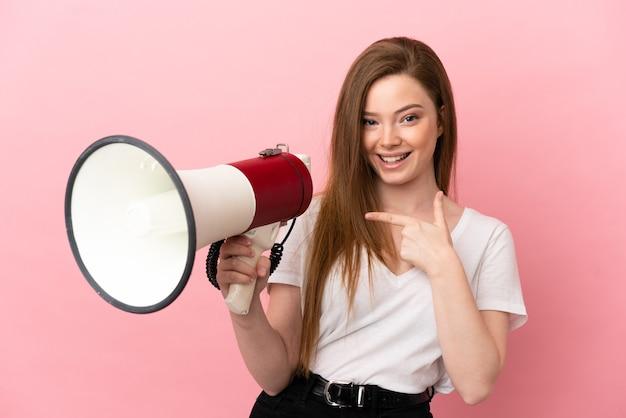 Teenager-mädchen über isoliertem rosa hintergrund, der ein megaphon hält und auf die seite zeigt