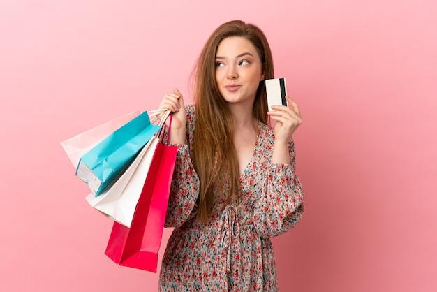 Teenager-mädchen über isoliertem rosa hintergrund, der einkaufstüten und eine kreditkarte hält und denkt
