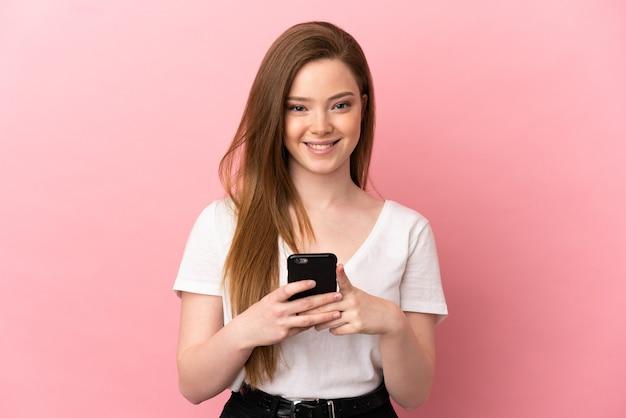 Teenager-mädchen über isoliertem rosa hintergrund, der in die kamera schaut und lächelt, während er das handy benutzt using